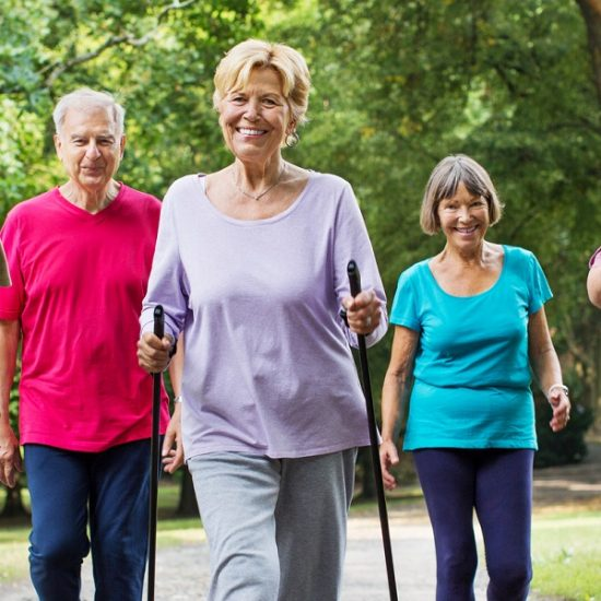 Group of active seniors walking on road through park in morning